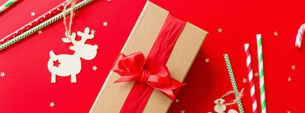 Eingewickeltes geschenk, holzspielzeug und papierstrohe auf rot