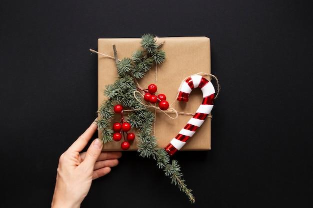 Eingewickeltes geschenk mit den weihnachtsdekorationen in der hand gehalten
