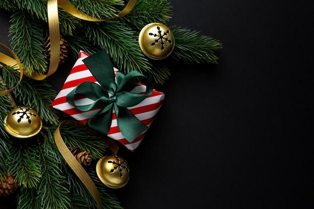 Eingewickeltes geschenk mit grüner schleife und kugeln auf dunklem hintergrund.