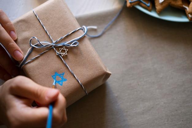 Eingewickeltes geschenk und traditionelles glückliches chanukka-symbol