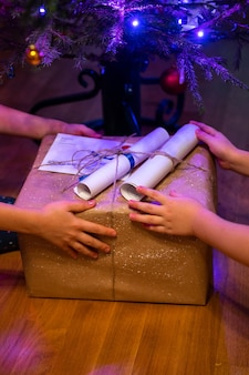 Eingewickeltes geschenk unter einem weihnachtsbaum in den händen der kinder zu hause. kleine geschwisterkinder geben sich gegenseitig geschenke.