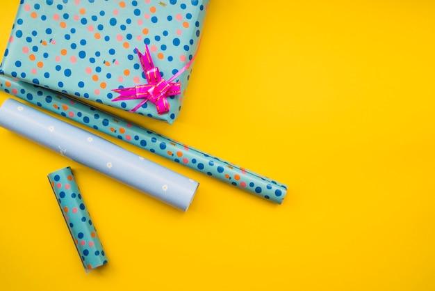 Eingewickeltes geschenkpapier mit geschenkbox auf gelbem hintergrund
