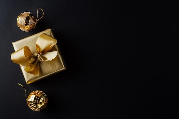 Eingewickeltes goldenes geschenk mit goldener schleife und kugeln auf schwarz. flache lage.