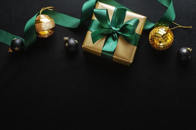 Eingewickeltes goldenes geschenk mit grüner schleife und kugeln auf dunkler oberfläche