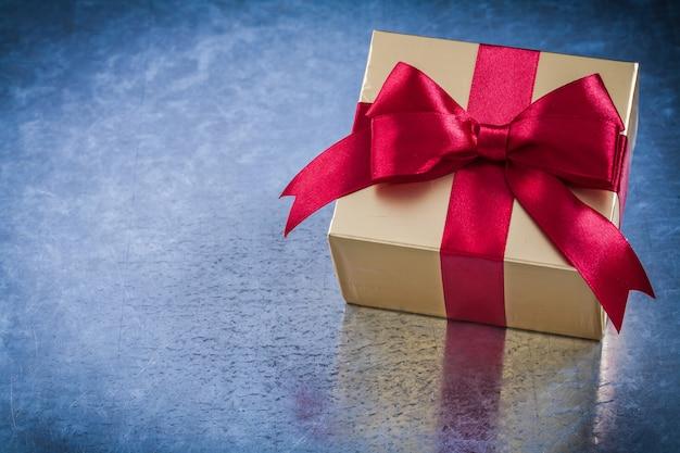 Eingewickeltes goldenes geschenk mit horizontaler ansicht des bogens der roten schleife