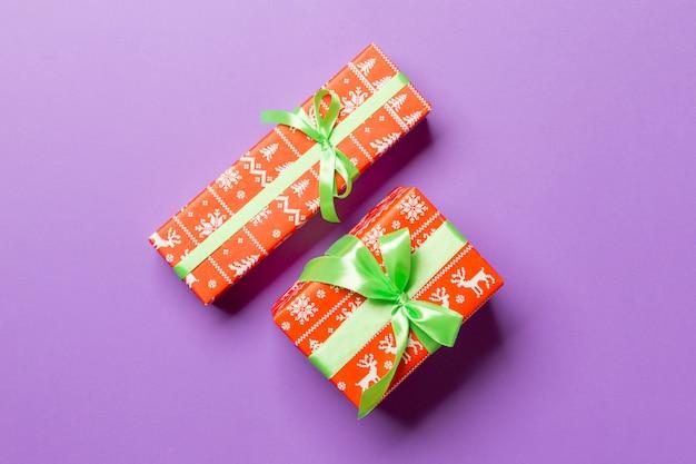 Eingewickeltes handgemachtes geschenk des weihnachten oder anderen feiertags im grünen papierband auf purpur. präsentkarton, dekorationsgeschenk auf farbiger tabelle, draufsicht