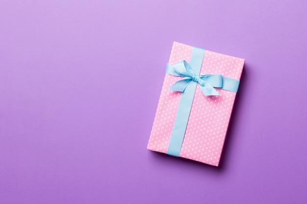 Eingewickeltes handgemachtes geschenk des weihnachten oder anderen feiertags im papier mit blauem band auf purpurrotem hintergrund