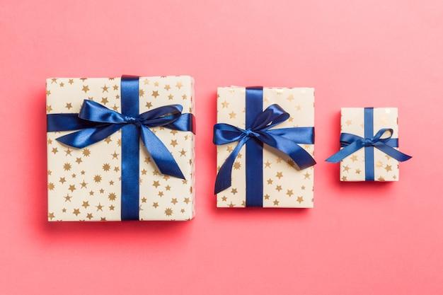 Eingewickeltes handgemachtes geschenk des weihnachten oder anderen feiertags im papier mit blauem band. präsentkarton, dekoration des geschenks auf farbiger tabelle, draufsicht
