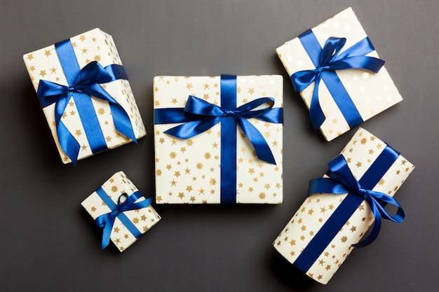 Eingewickeltes handgemachtes geschenk des weihnachten oder anderen feiertags im papier mit blauem band