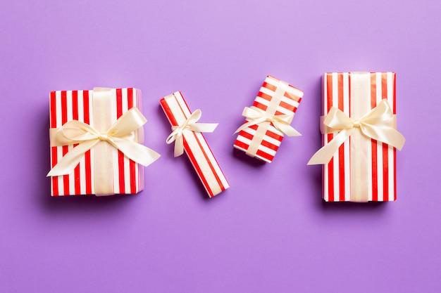 Eingewickeltes handgemachtes geschenk des weihnachten oder anderen feiertags im papier mit gelbem band auf purpurrotem hintergrund. präsentkarton, dekoration des geschenks auf farbiger tabelle, draufsicht