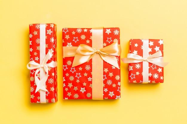 Eingewickeltes handgemachtes geschenk des weihnachten oder anderen feiertags im papier mit goldband auf gelbem hintergrund