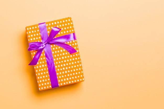 Eingewickeltes handgemachtes geschenk des weihnachten oder anderen feiertags im papier mit purpurrotem band auf orange hintergrund