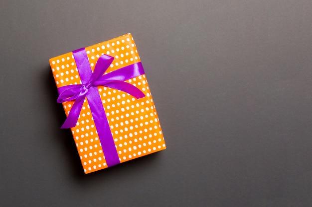 Eingewickeltes handgemachtes geschenk des weihnachten oder anderen feiertags im papier mit purpurrotem band auf schwarzem hintergrund