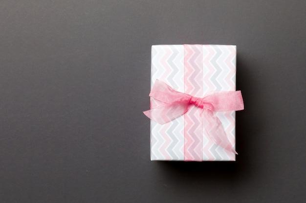 Eingewickeltes handgemachtes geschenk des weihnachten oder anderen feiertags im papier mit rosa band