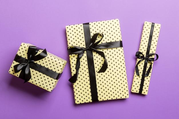 Eingewickeltes handgemachtes geschenk des weihnachten oder anderen feiertags im papier mit schwarzem band auf purpurrotem hintergrund. präsentkarton, dekoration des geschenks auf farbiger tabelle, draufsicht
