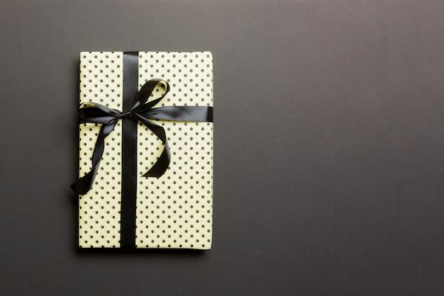 Eingewickeltes handgemachtes geschenk des weihnachten oder anderen feiertags im papier mit schwarzem band auf schwarzem hintergrund