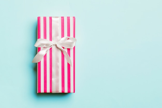 Eingewickeltes handgemachtes geschenk des weihnachten oder anderen feiertags im papier mit weißem band auf blauem hintergrund