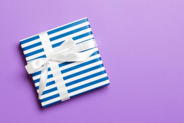 Eingewickeltes handgemachtes geschenk des weihnachten oder anderen feiertags im papier mit weißem band auf purpurrotem hintergrund