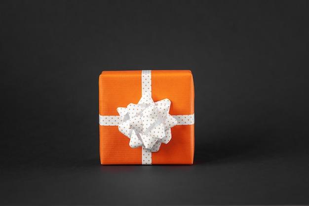 Eingewickeltes handgemachtes geschenk in orangefarbenem papier mit schleife auf schwarzem hintergrund. geschenkbox mit kopienraum.