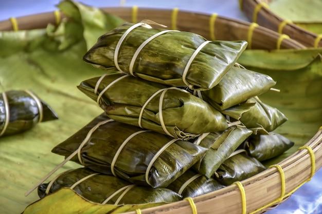 Eingewickeltes lebensmittel der thailändischen art bananenblatt, gemacht vom klebrigen reis, vom schweinefleisch und von der erdnuss