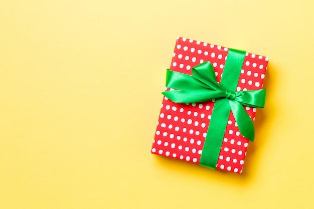 Eingewickeltes weihnachten oder anderes handgemachtes geschenk des feiertags im papier mit grünem band auf gelbem hintergrund. präsentkarton, dekoration des geschenks auf farbiger tabelle, draufsicht mit copyspace