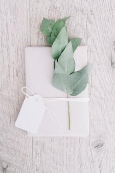 Eingewickeltes Weißgeschenk mit leerem Tag und Zweig auf hölzernem Hintergrund