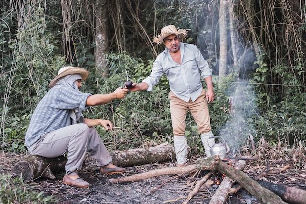 Einheimische bauern trinken mate-tee zu ihrer pause in einer rustikalen teekanne.