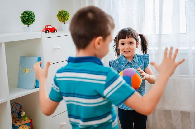 Einheimische kinder, ein junge und ein mädchen, spielen in einem kinderspielzimmer und werfen einen ball