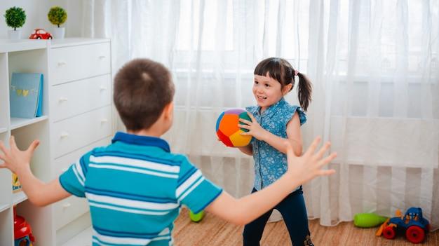 Einheimische kinder, ein junge und ein mädchen, spielen in einem kinderspielzimmer und werfen einen ball.