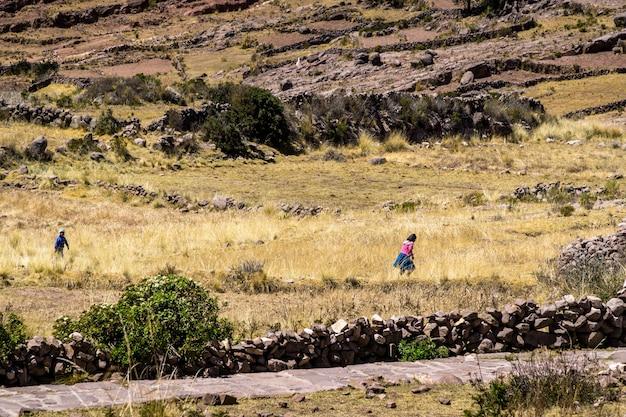 Einheimische mädchen und jungen, die nach hause auf der insel taquile im titicacasee per laufen