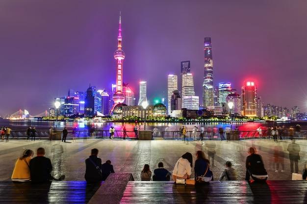 Einheimische und touristen, die am huangpu-flussufer die promenade in shanghai, china sich entspannen und besichtigen