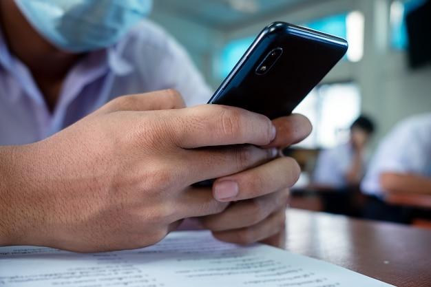 Einheitlicher student, der smartphone und tragende gesichtsmaske im klassenzimmer verwendet