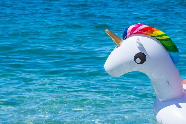 Einhornschwimmenrohr auf wasserhintergrund. aufblasbares einhorn. fantasie-schwimmring für sommerpool oder meer.
