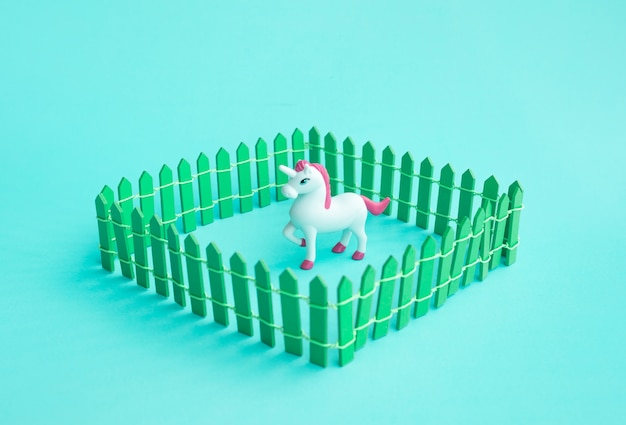 Einhornspielzeugmodell im zaun auf farbigem hintergrund