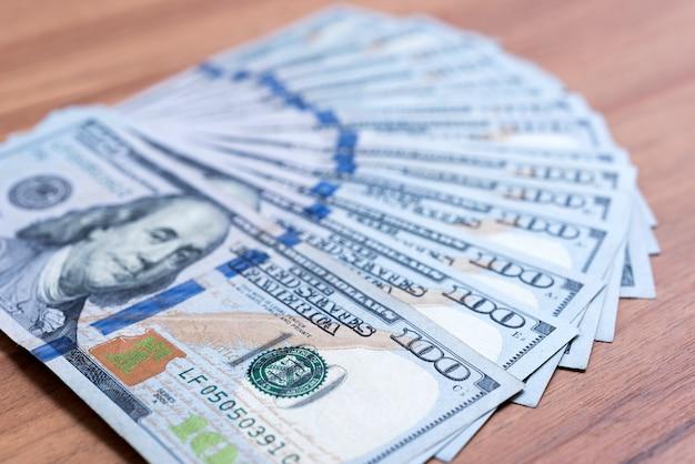 Einhundert dollar banknoten auf holzoberfläche gestapelt