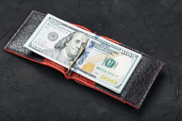 Einhundert dollar in einer roten handtasche an einer schwarzen wand