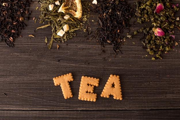 Einige ansichten des tees und der plätzchenaufschrift auf einem holztisch