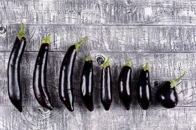 Einige auberginen nach größe sortiert, flach liegend.
