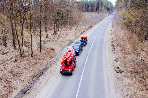 Einige autos mit kajaks auf dem dachgepäckträger, der auf die straße unter bäumen fährt