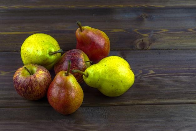 Einige birnen und äpfel auf einem holztisch