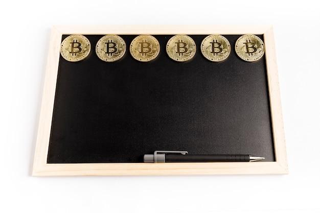 Einige bitcoin goldmünzen nahe bei einem stift auf einer schwarzen tafel