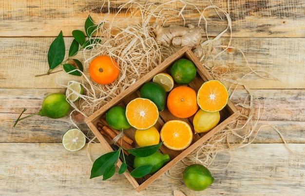 Einige clementinen mit limetten und mandarinen in einer holzkiste auf holzbrett