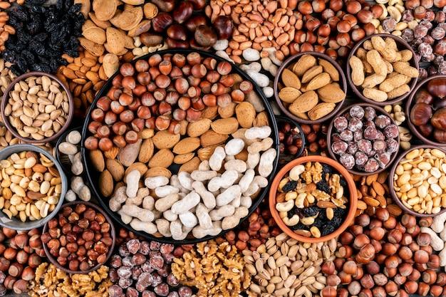 Einige der verschiedenen nüsse und getrockneten früchte mit pekannuss, pistazien, mandeln, erdnüssen, cashewnüssen, pinienkernen in verschiedenen schalen und schwarzer pfanne flach liegen.