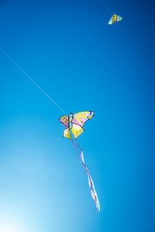 Einige drachen der spiele der sommerkinder, die in den blauen himmel fliegen.