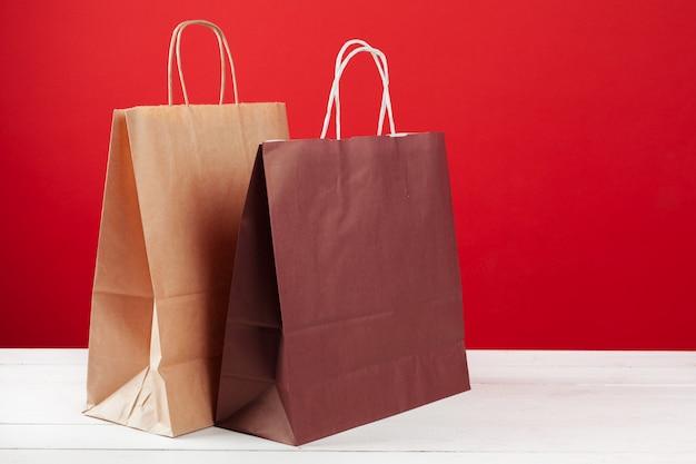 Einige einkaufstaschen mit exemplarplatz auf rotem hintergrund