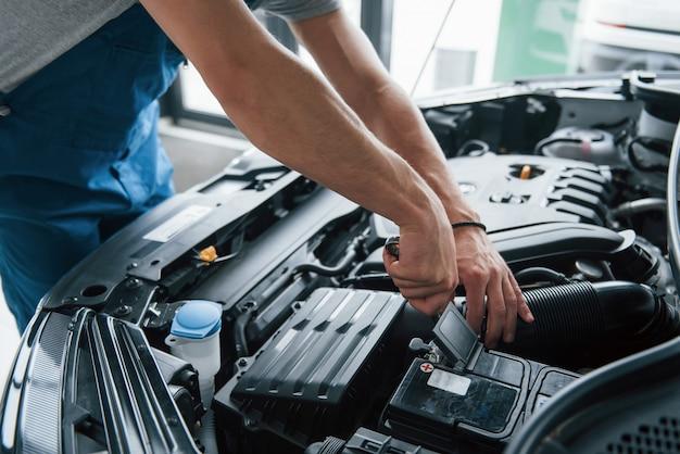 Einige elektronische teile. reparatur des autos nach einem unfall. mann, der mit motor unter der haube arbeitet