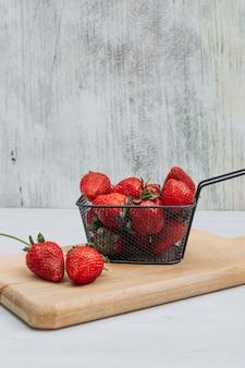 Einige erdbeeren mit mehreren erdbeeren um ihn herum in einem schwarzen korb auf hölzernem schneidebrett und weißem hintergrund, seitenansicht