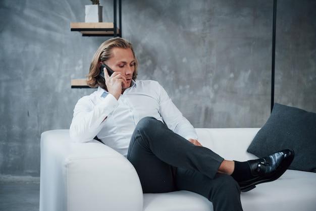 Einige ernsthafte deals stehen an. porträt eines jungen geschäftsmannes mit dem langen haar, das auf der couch sitzt und an einem handy spricht