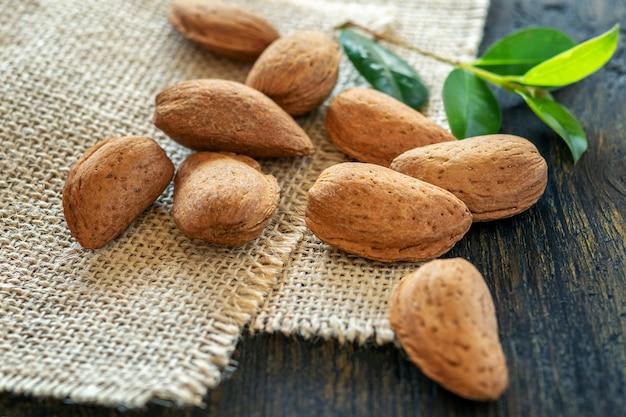 Einige frische reife braune mandeln auf dem sack und auf dem natürlichen holztisch.