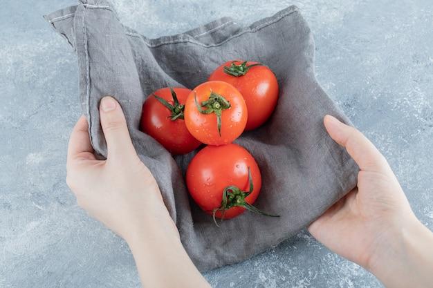 Einige frische tomaten auf einer grauen tischdecke.